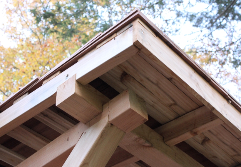 The support posts, the header, and the roof rafters all join with half-lap or psuedo mortise and tenon joinery.